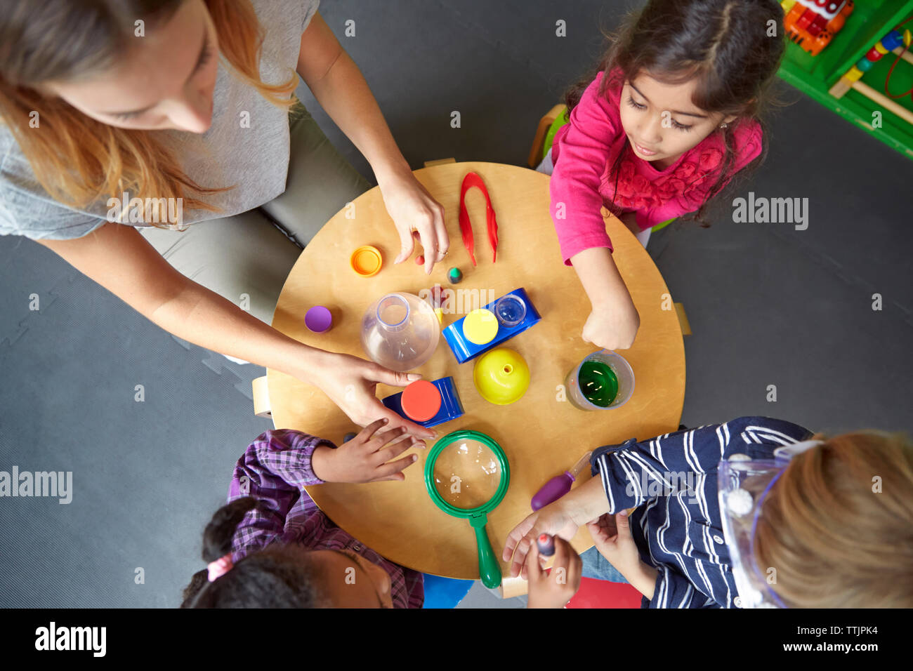 Overhead view of teacher assisting children in science experiment at preschool Stock Photo