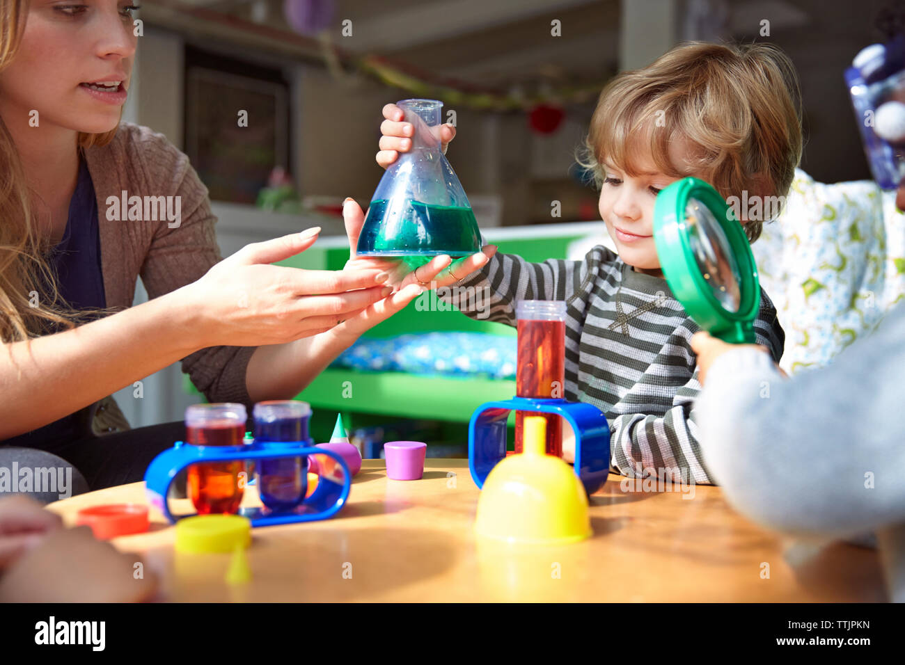 Teacher guiding students in doing science experiment at preschool Stock Photo
