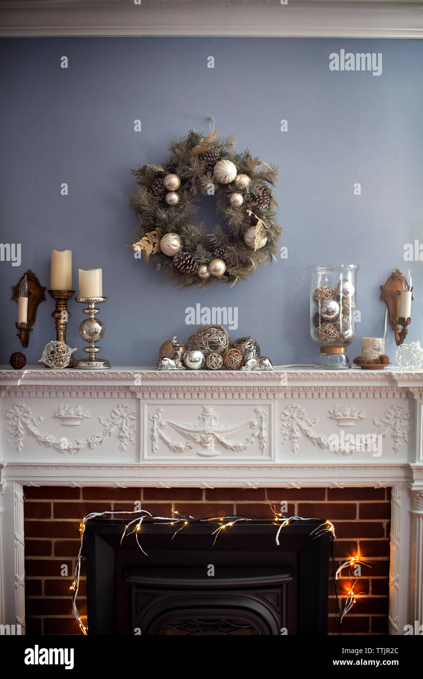 Christmas wreaths hanging on wall over fireplace Stock Photo