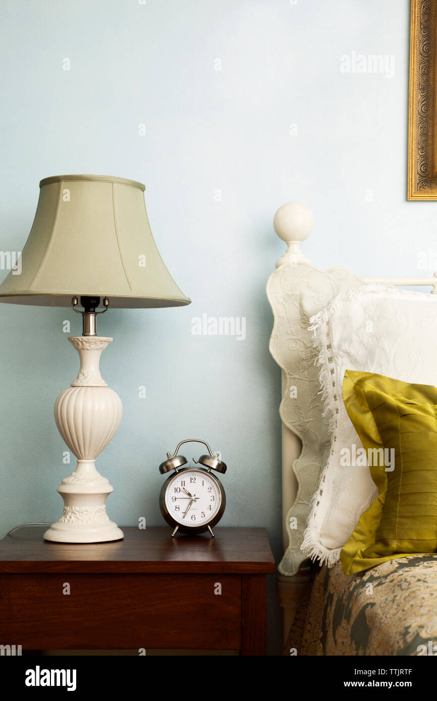 Alarm clock and lamp on side table in bedroom Stock Photo