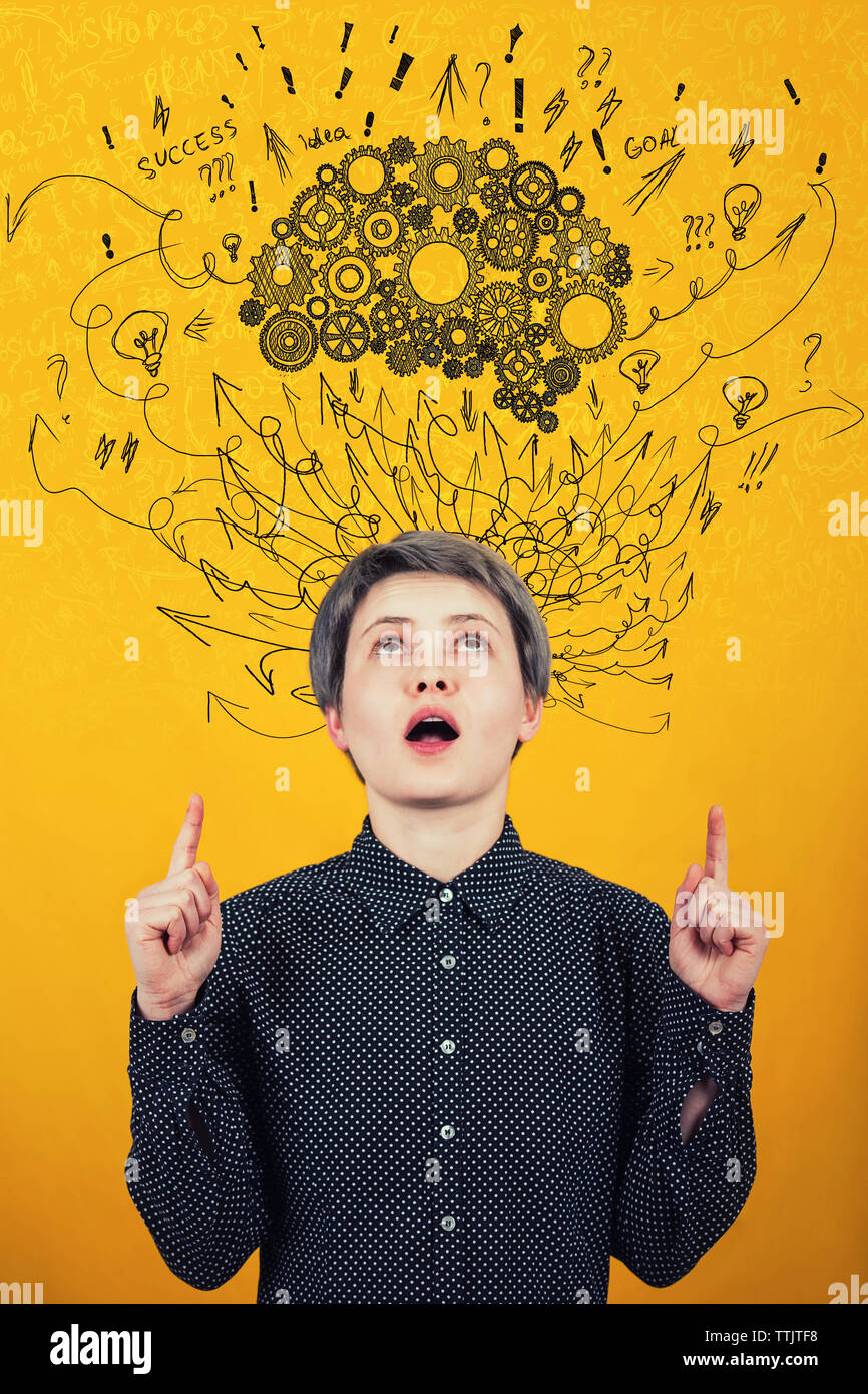 Young woman points forefingers up, looking astonished and curious with mouth open at cogwheel brain above head. Hard thinking, arrows and curves mess Stock Photo