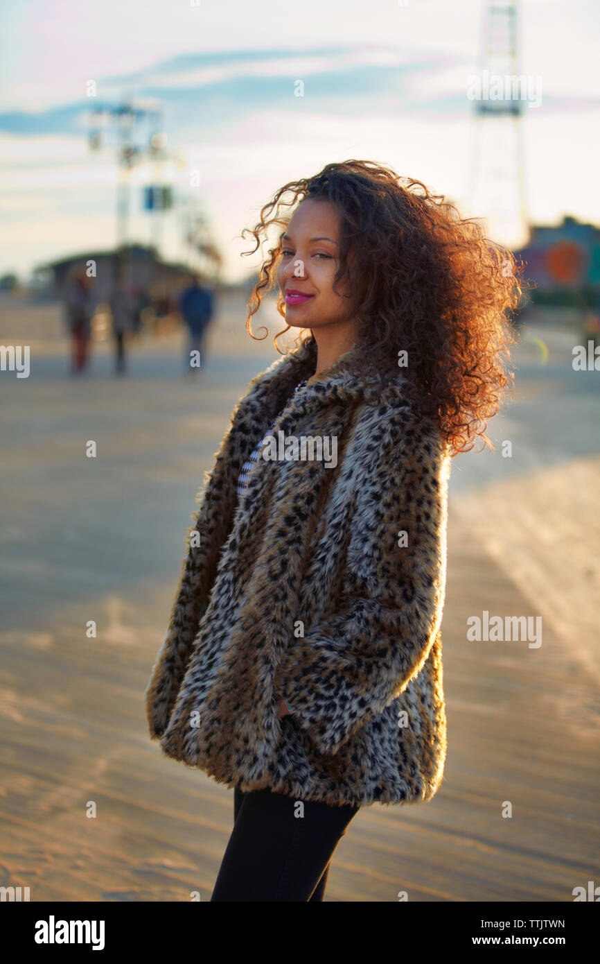 9ab17d3331b74 Smiling woman with curly hair wearing fur coat while standing at Coney  Island - Stock Image