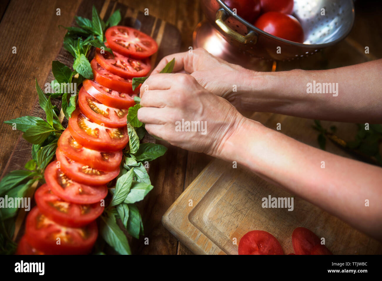 Cropped image of woman garnishing tomato salad with mint leaves at table Stock Photo