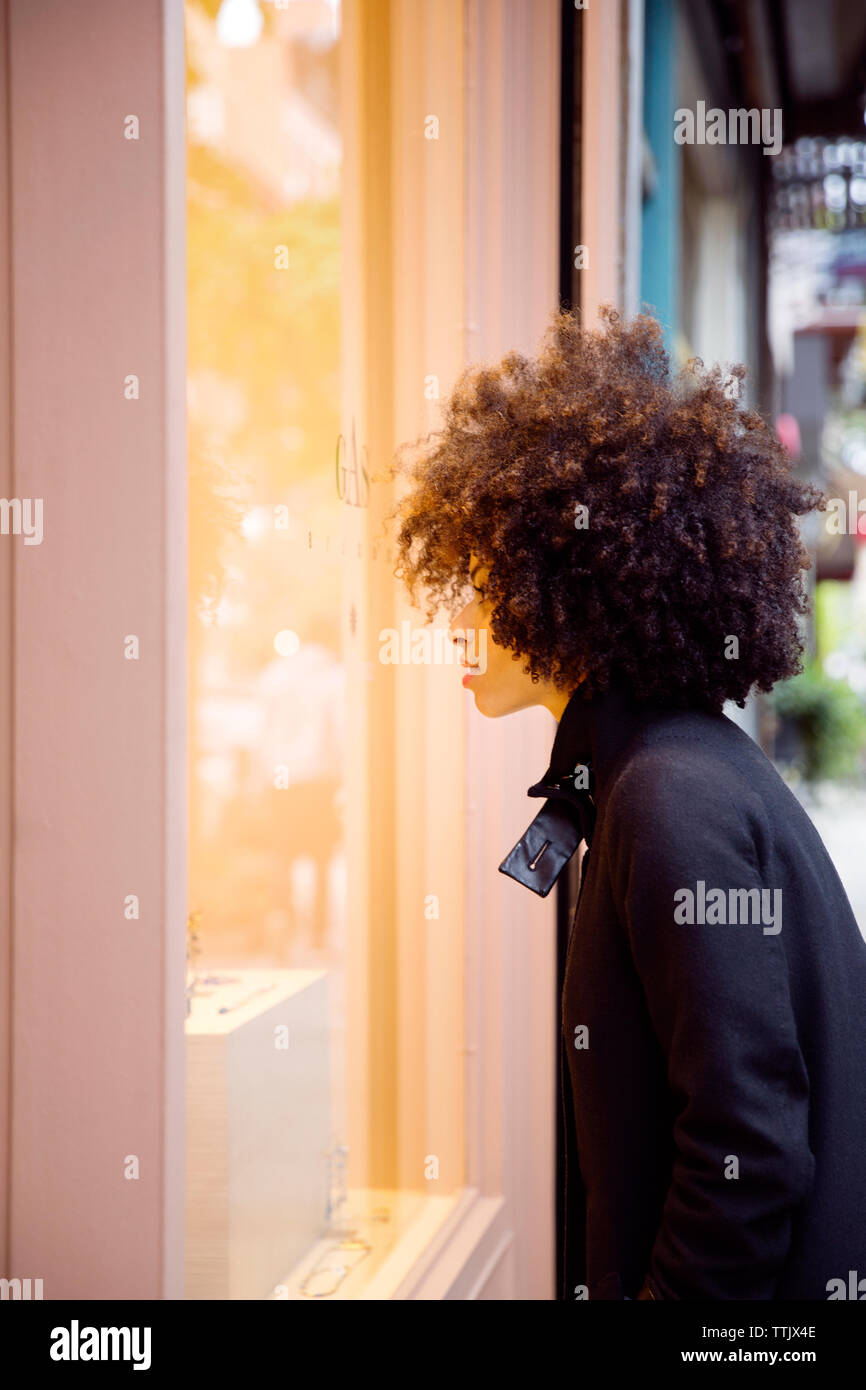 Side view of woman window shopping in city - Stock Image