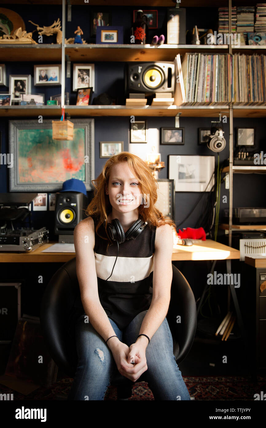 Portrait of happy female DJ sitting at sound recording studio Stock Photo