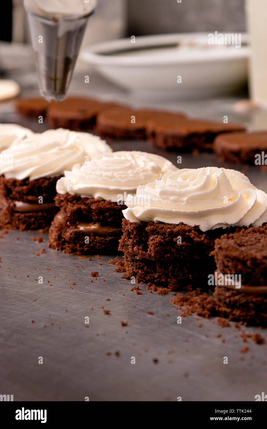 Close-up of whipped cream chocolate sponge cakes at kitchen counter Stock Photo