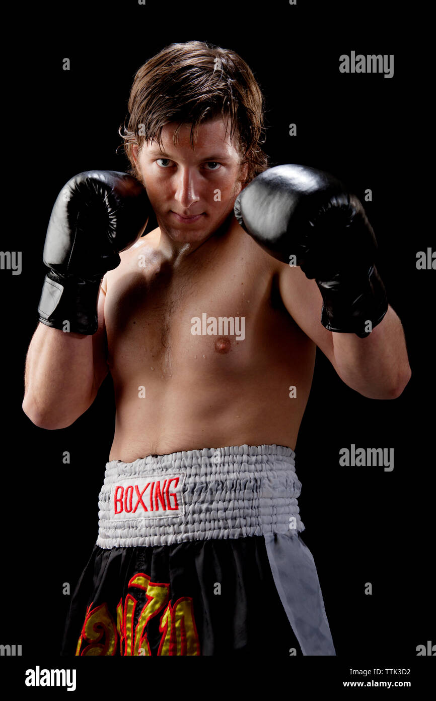 Portrait of boxer against black background - Stock Image