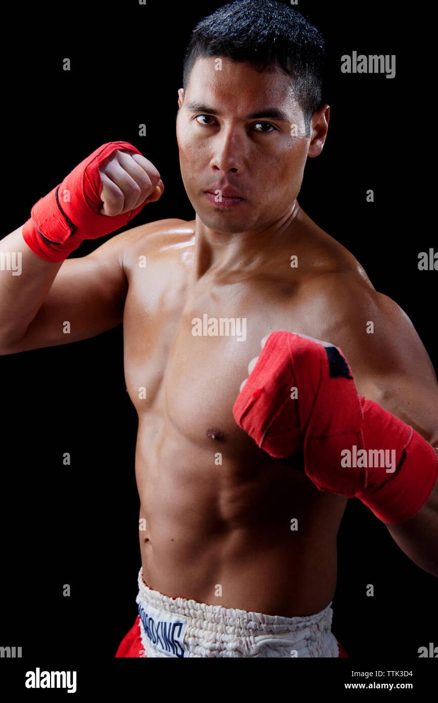 Portrait of shirtless confident boxer against black background - Stock Image