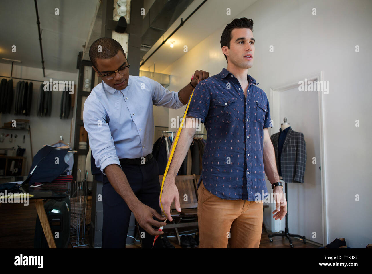 Tailor taking measures of customer at workshop - Stock Image