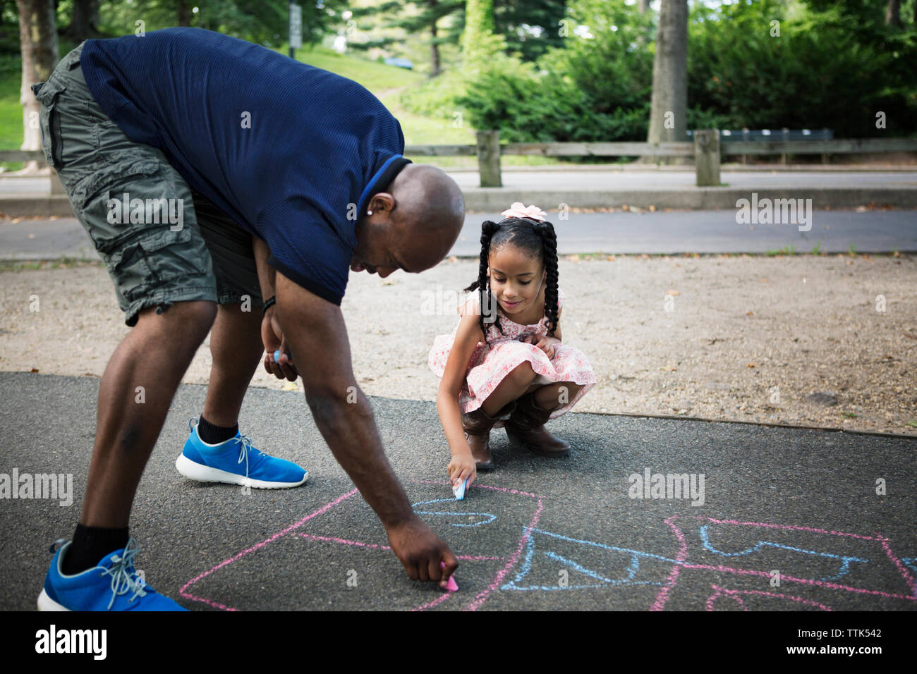 Father and daughter drawing hopscotch on road at park - Stock Image