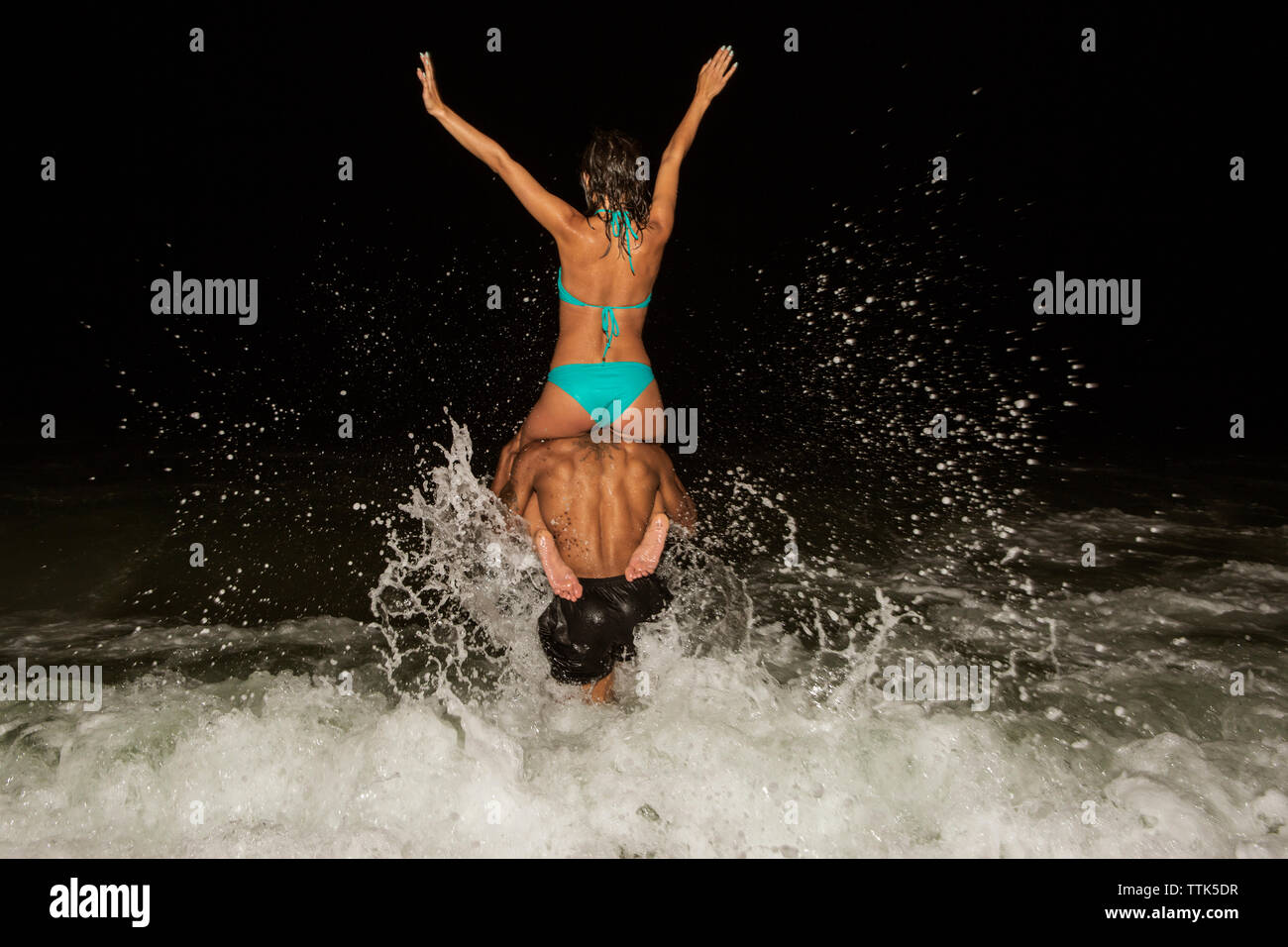 Rear view of man carrying woman on shoulders in sea at night - Stock Image