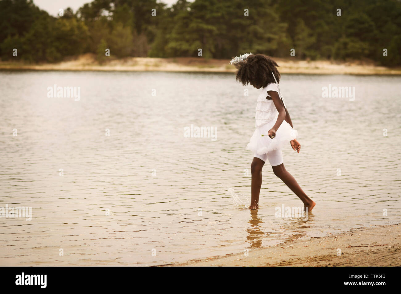 Side view of girl disguise as angel walking by lake - Stock Image