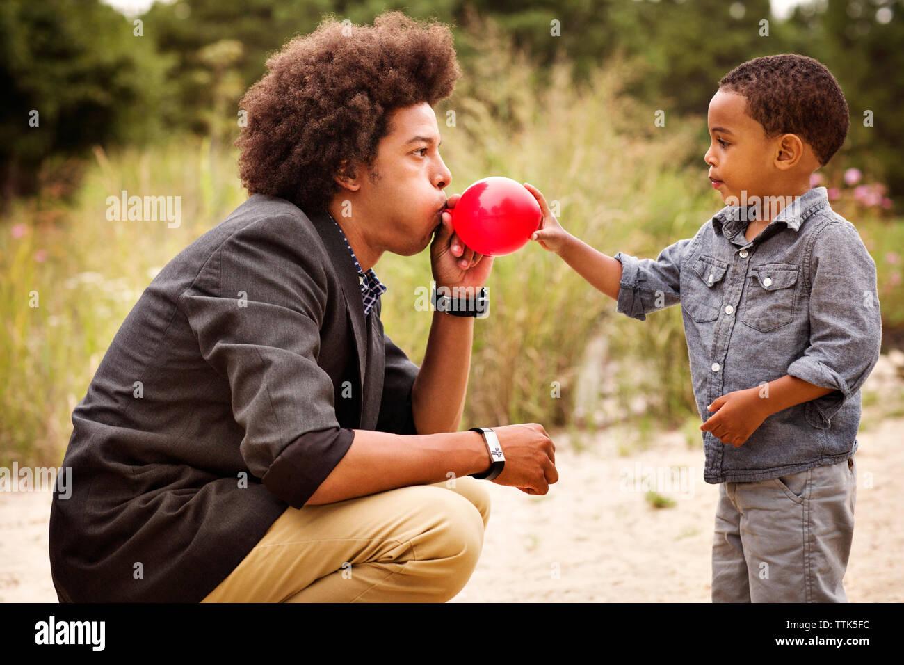 Man crouching while blowing balloon for brother - Stock Image