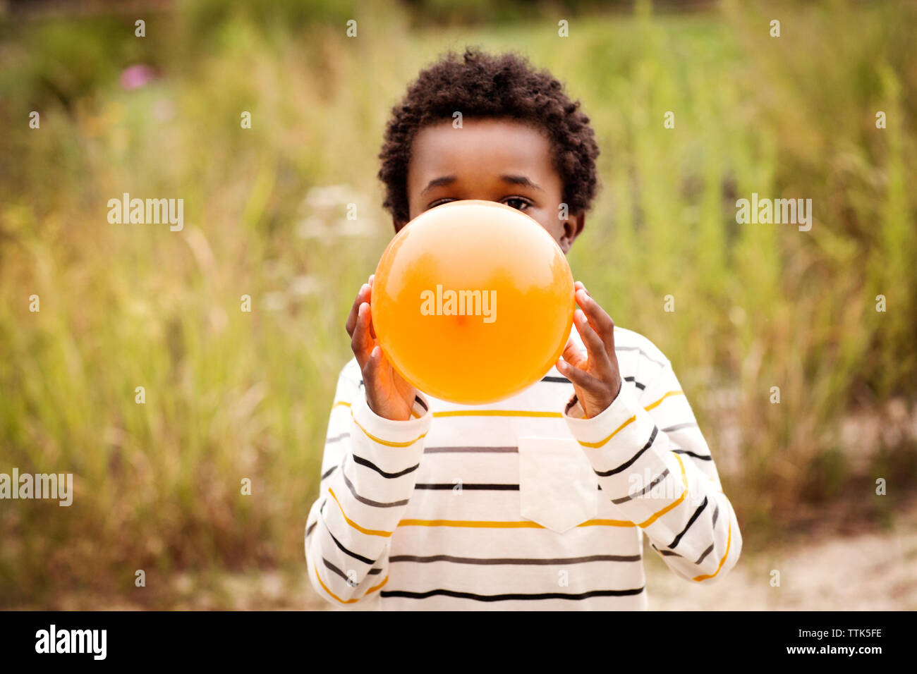 Boy blowing balloon while standing against grass field - Stock Image