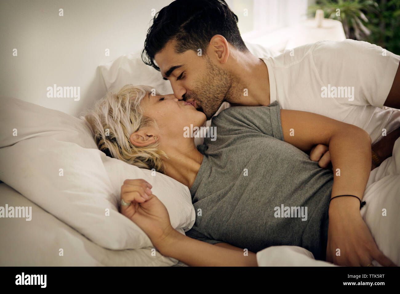 Young couple kissing on bed at home - Stock Image