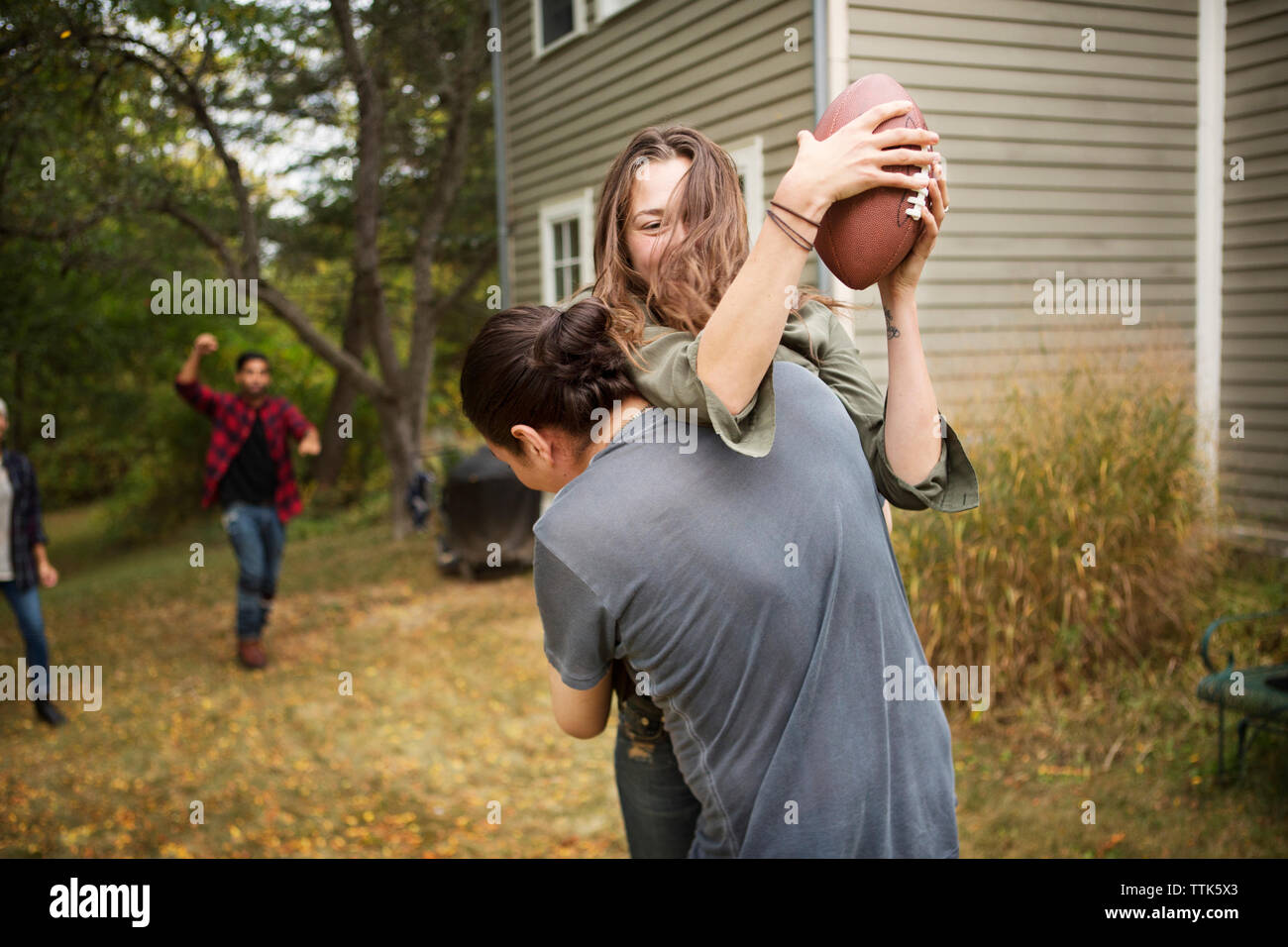 Couple playing football with friends on field Stock Photo