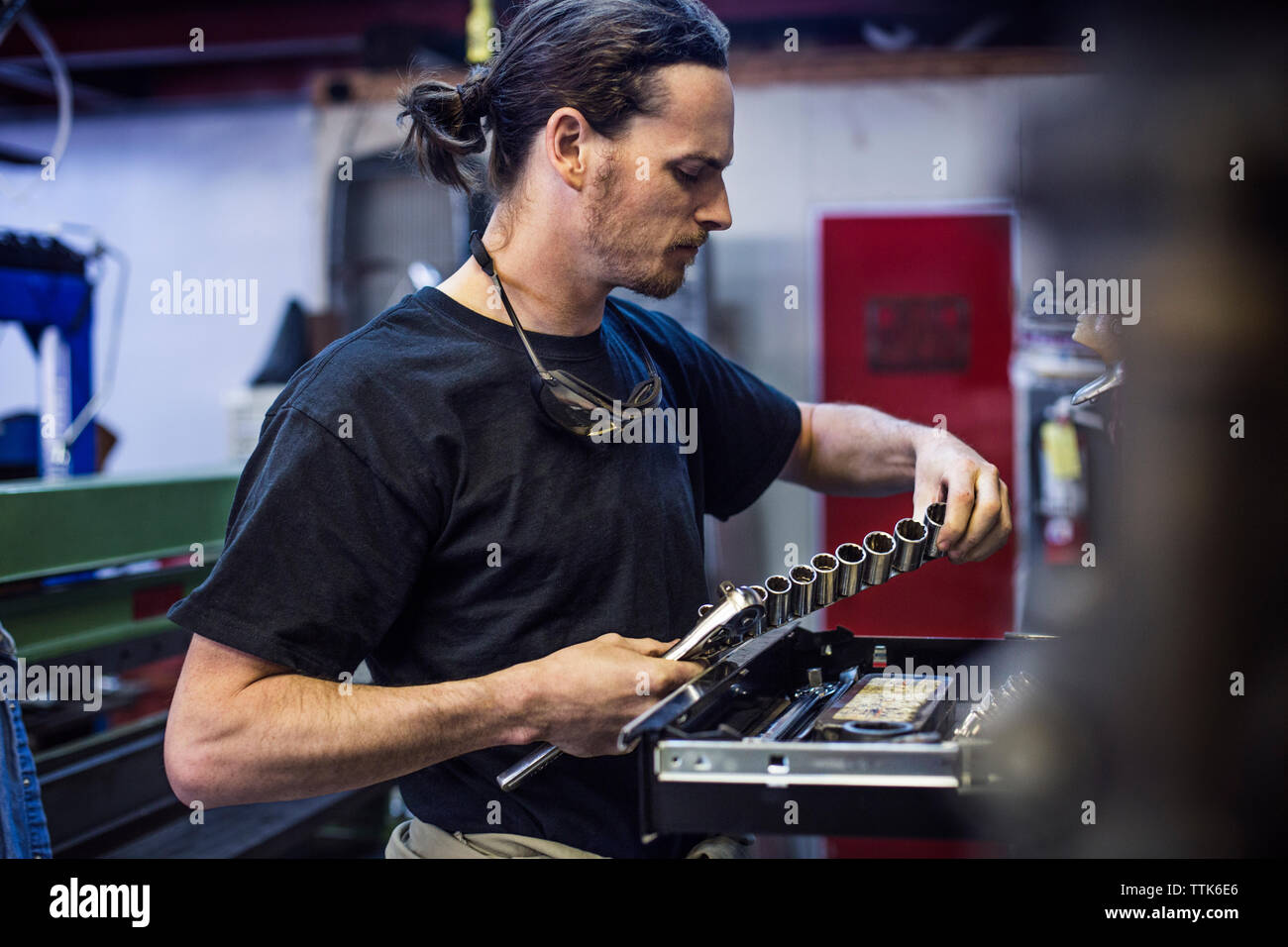 Mechanic holding hand tool at auto repair shop - Stock Image