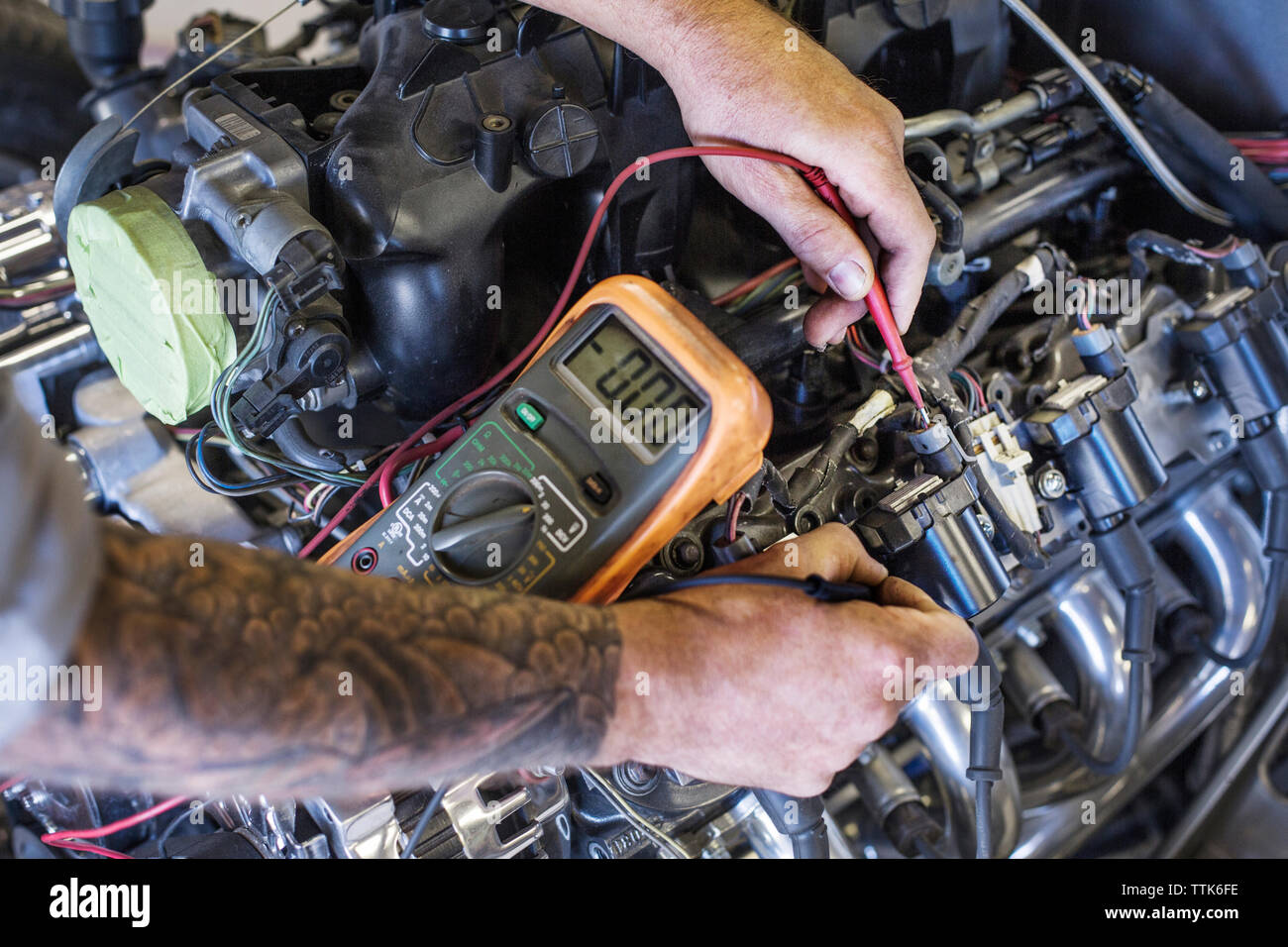 Cropped image of hands examining car engine with multimeter in auto repair shop - Stock Image
