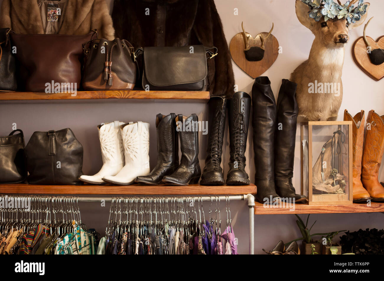 Various boots and purses displayed in boutique - Stock Image
