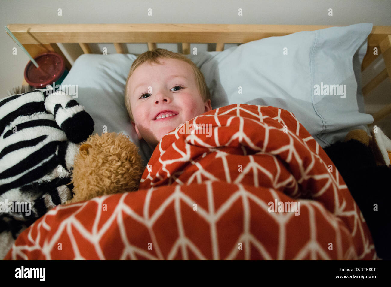 High angle portrait of smiling cute boy lying on bed at home - Stock Image