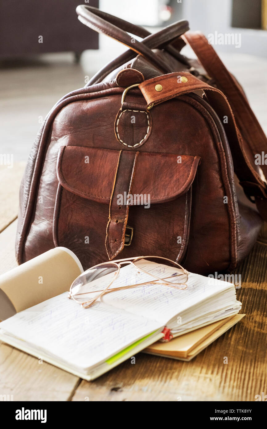 Leather bag and books on table at home office - Stock Image