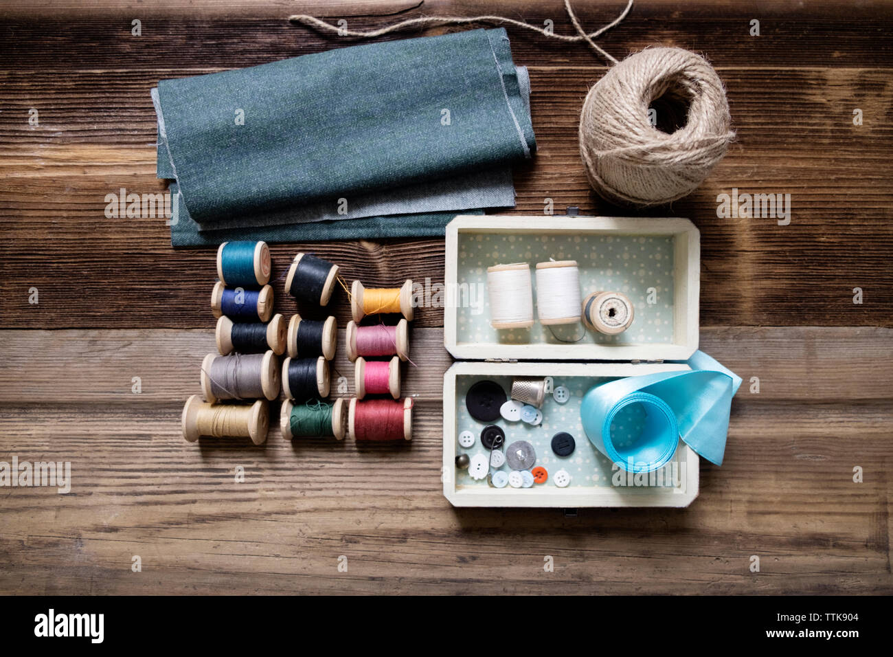 Overhead view of fabric with sewing equipment on table Stock Photo