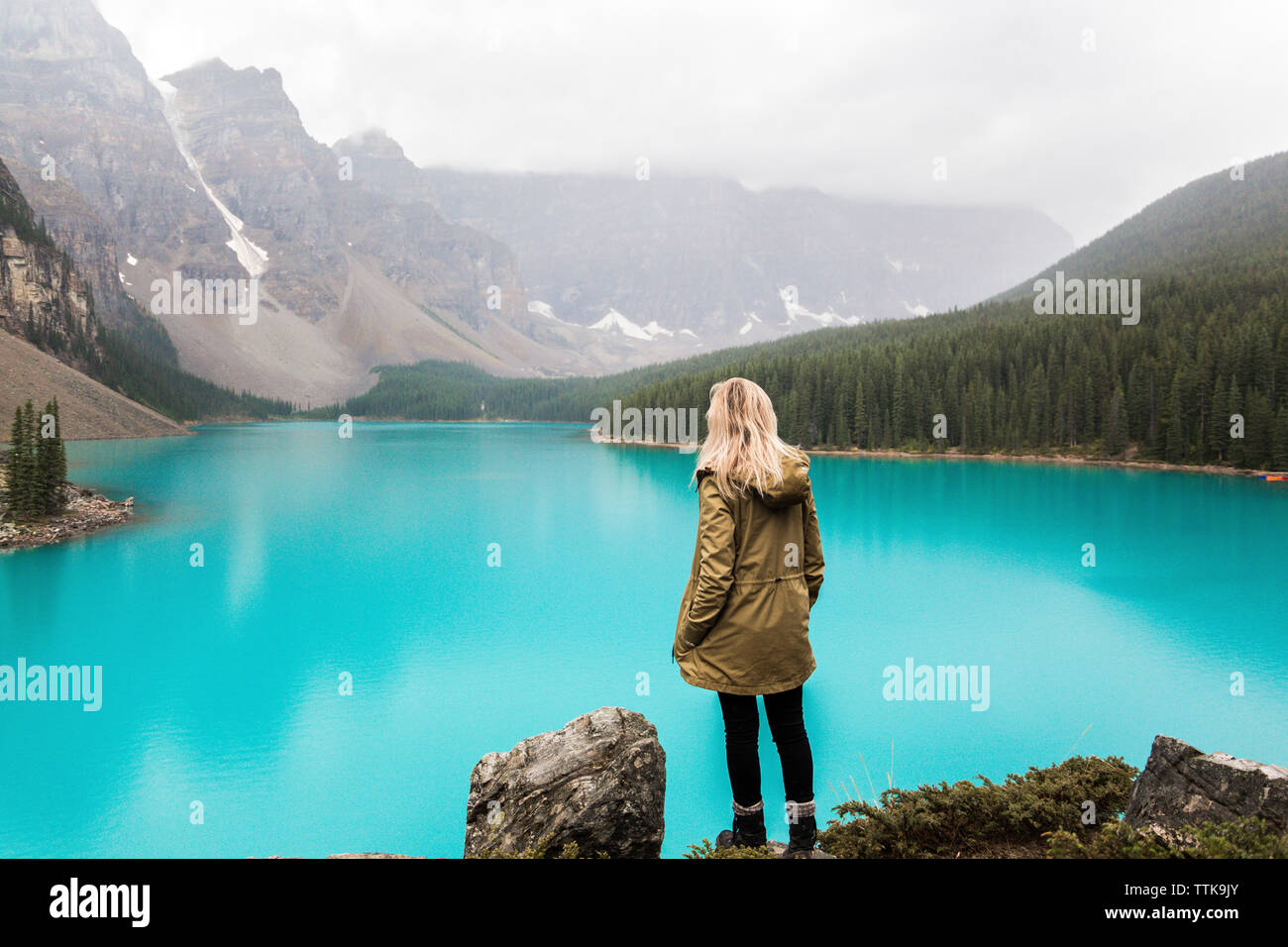 Rear view of female hiker with hand in pocket standing by Moraine Lake against mountains at Banff National Park Stock Photo