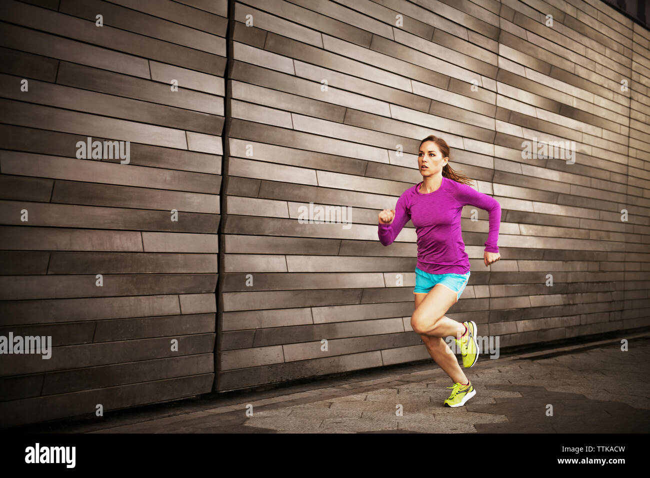 Woman jogging on sidewalk by wall - Stock Image