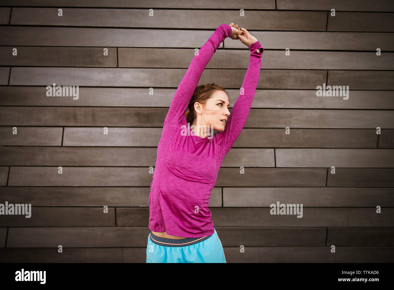 Mid adult woman stretching against wall - Stock Image