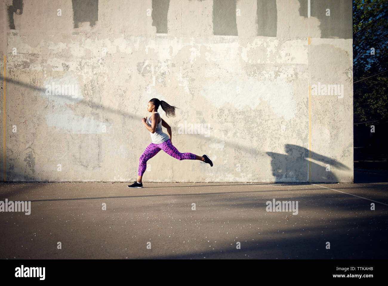 Woman jogging on street by wall - Stock Image