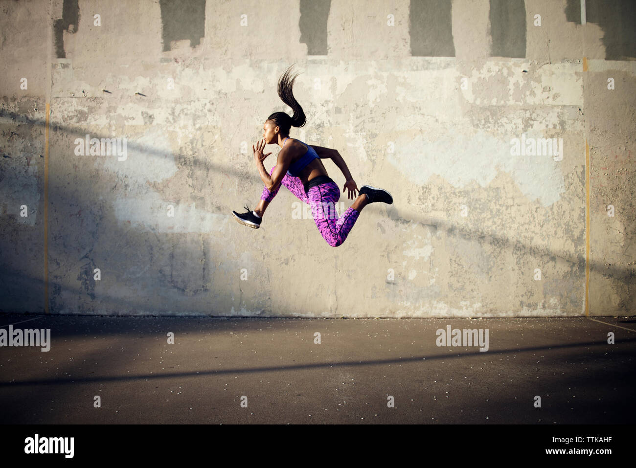 Side view of woman jumping in mid-air against wall - Stock Image