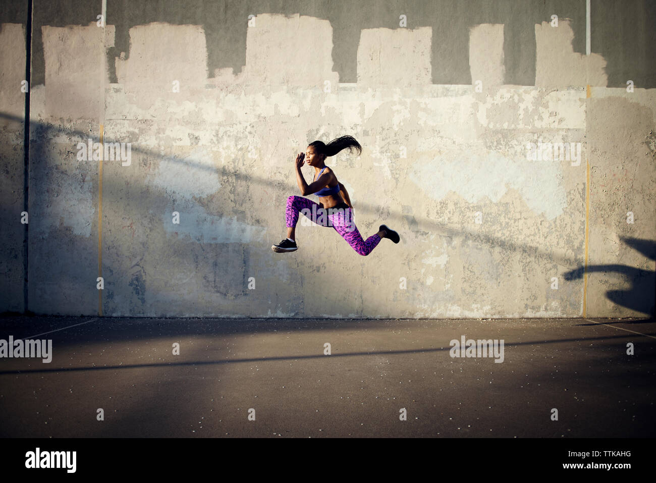 Side view of sportswoman jumping in mid-air against wall - Stock Image