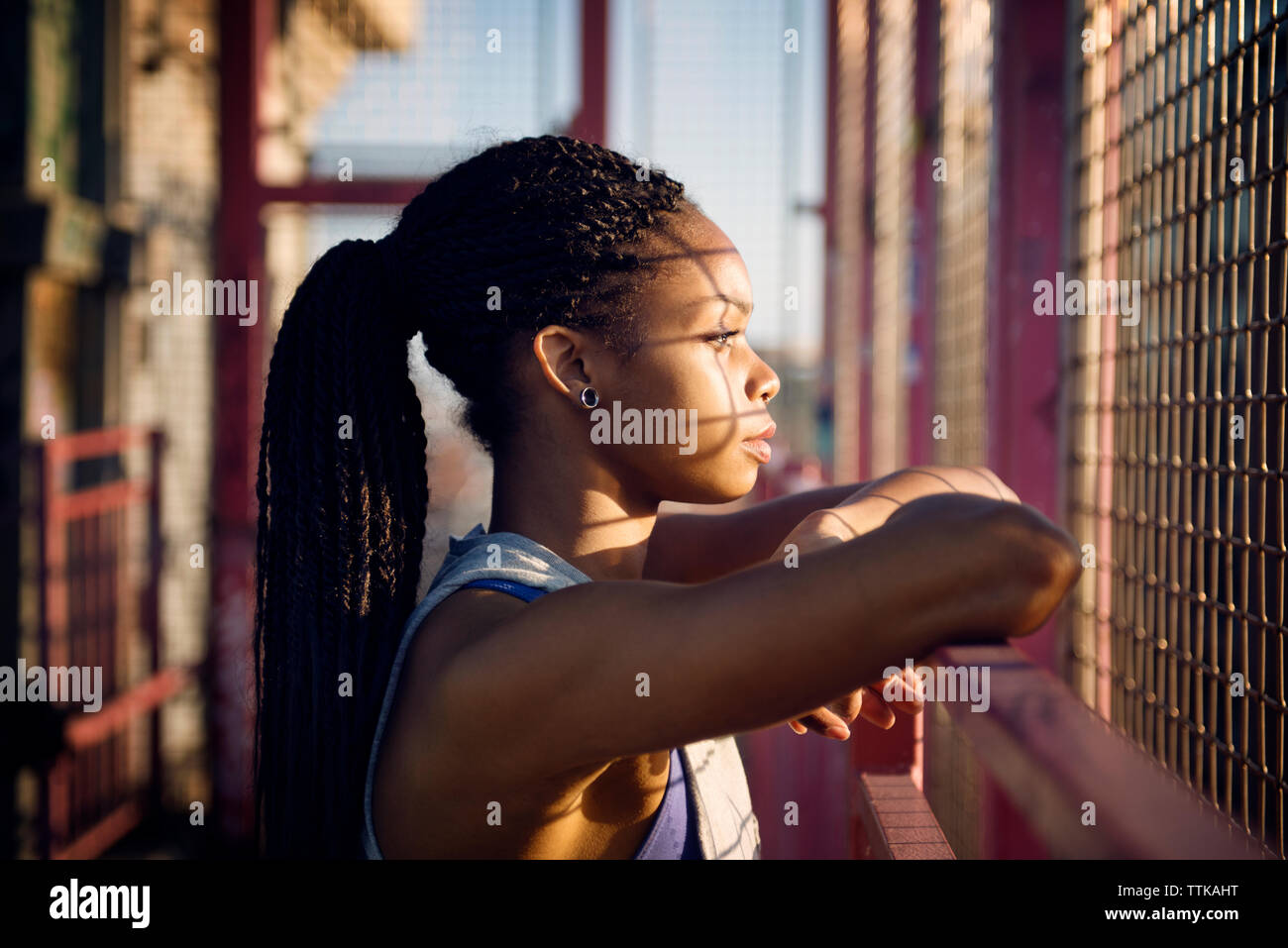 Thoughtful woman standing by fence on sunny day - Stock Image