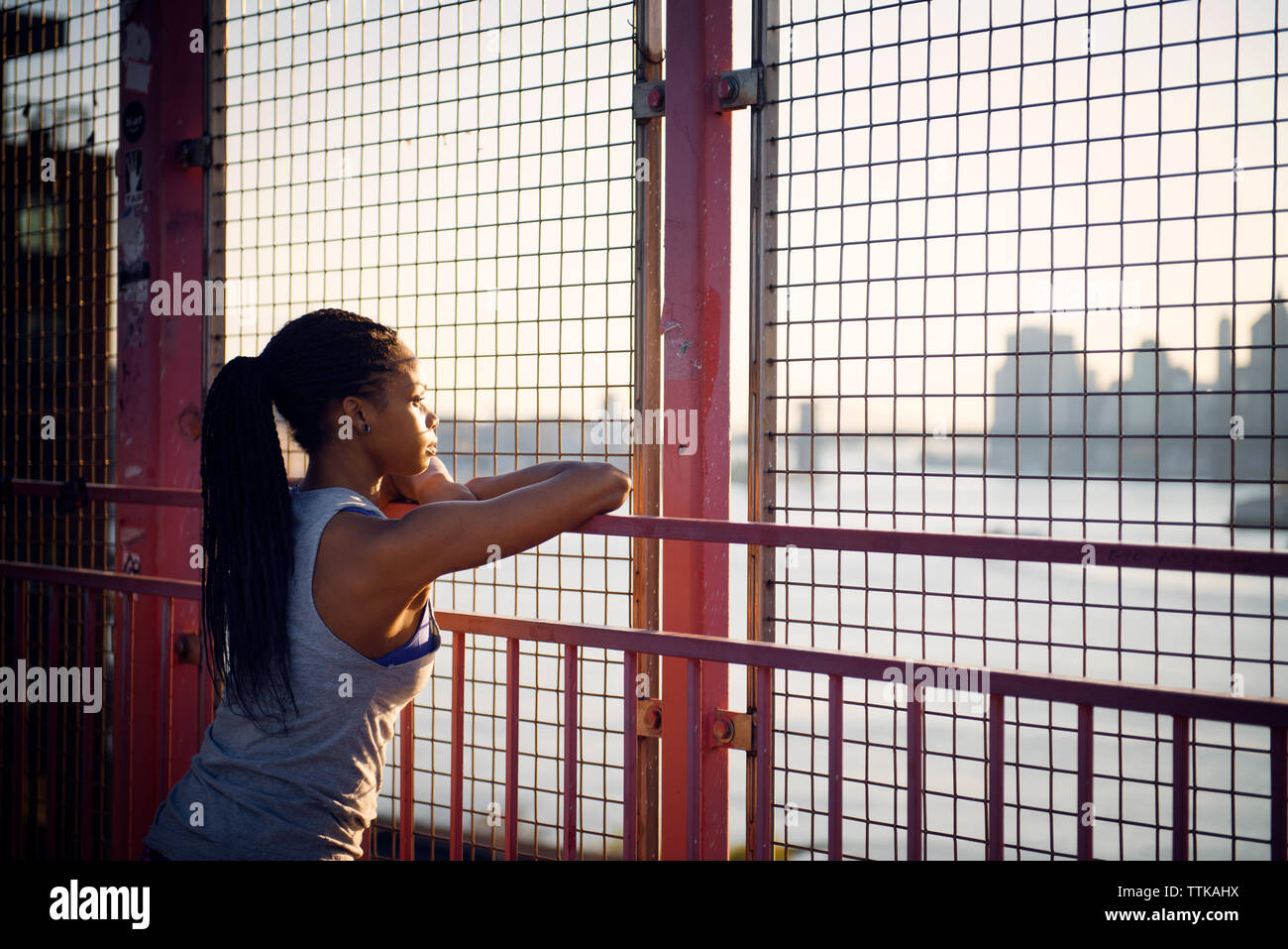 Thoughtful young woman standing by fence on sunny day - Stock Image