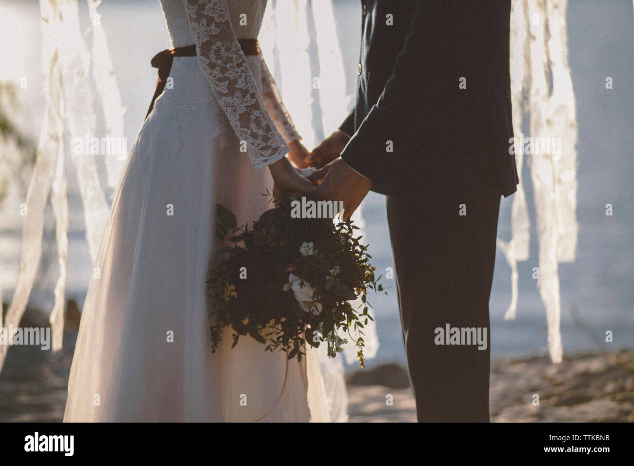 Midsection of wedding couple holding bouquet while standing at beach during sunset - Stock Photo
