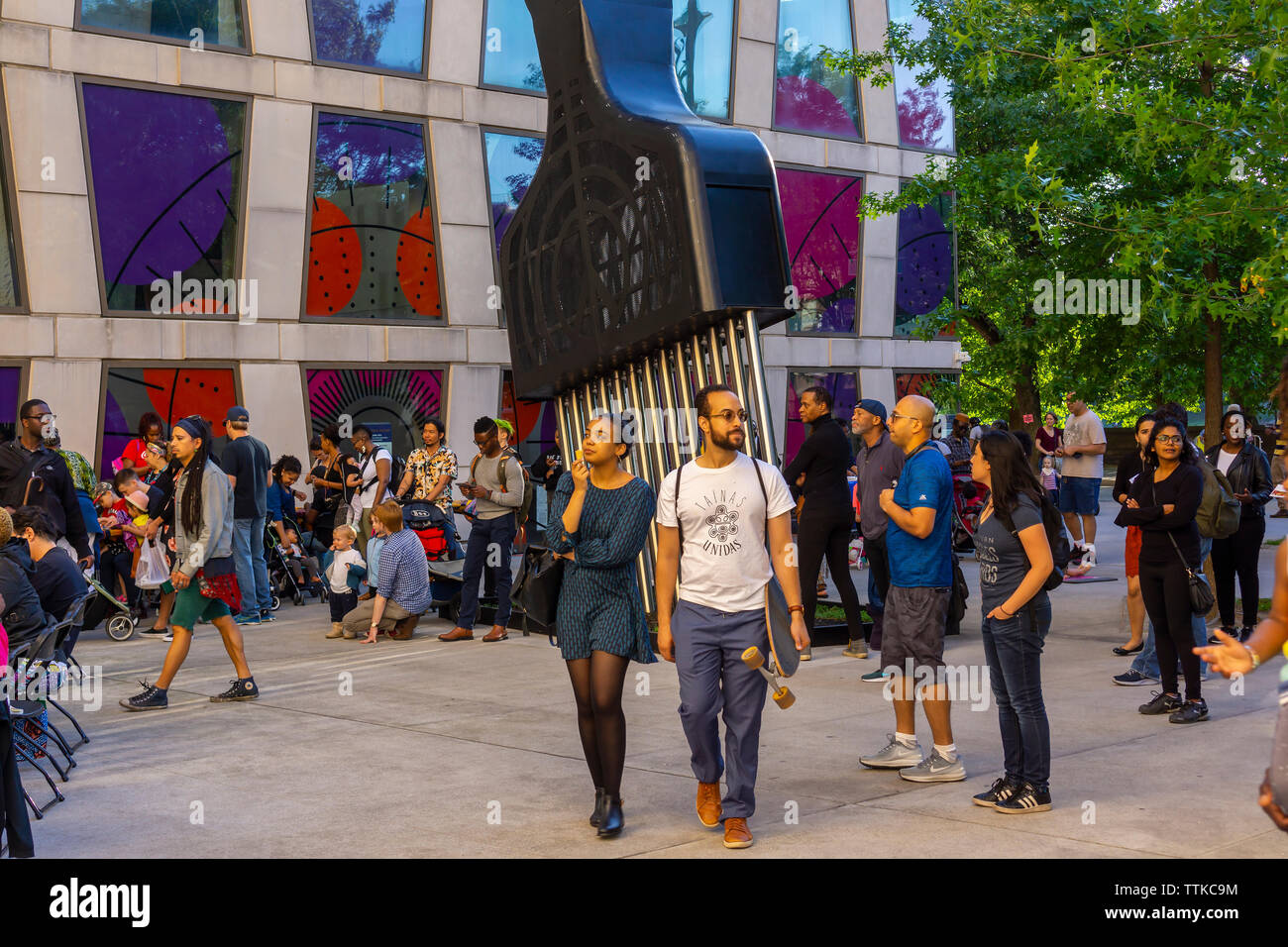 """Crowds around Hank Willis Thomas' """"All Power to All People"""" in the plaza of the Africa Center on Fifth Avenue at the edge of Harlem during the Museum Mile festival on Tuesday, June 11, 2019.   (© Richard B. Levine) - Stock Image"""