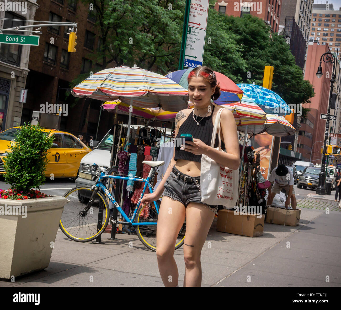 A distracted millennial, engrossed in her smartphone in New York on Friday, June 7, 2019.  (© Richard B. Levine) - Stock Image