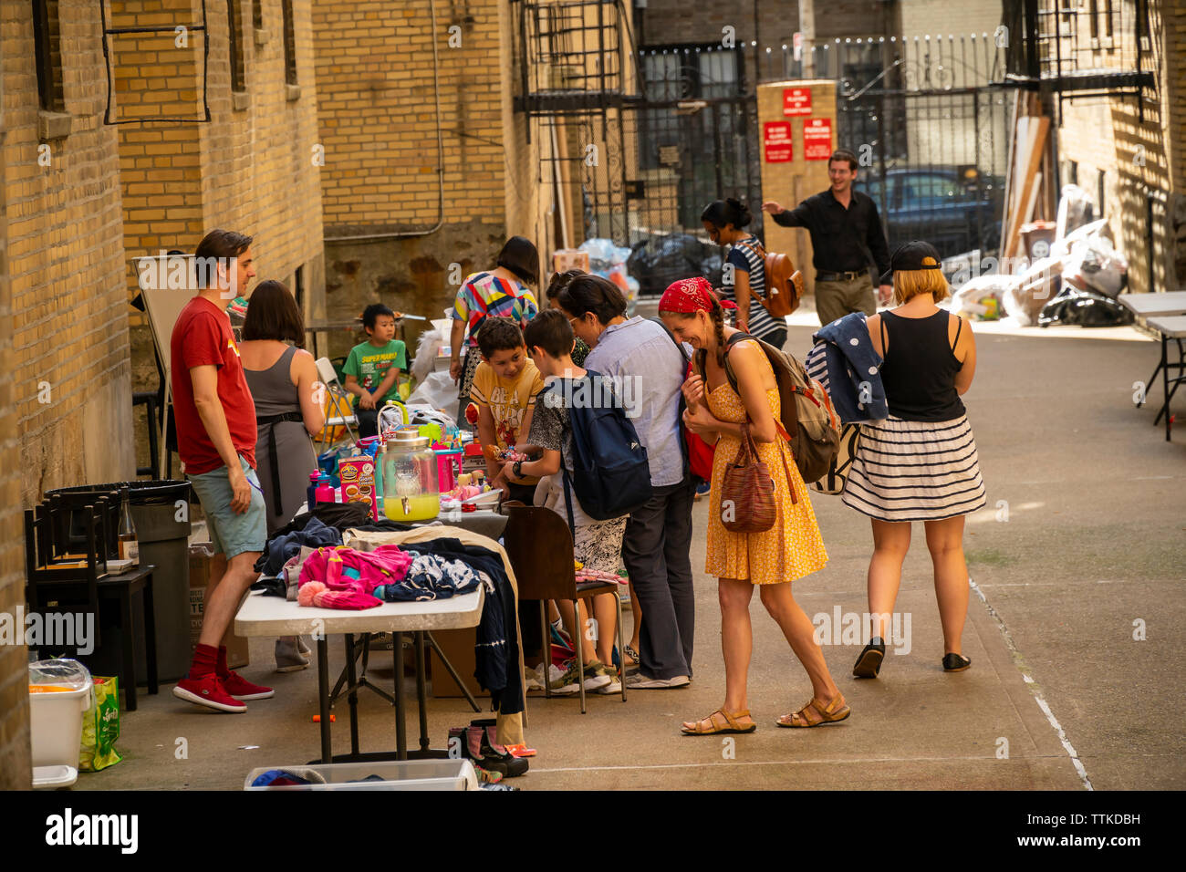 Shoppers search for bargains at an apartment building stoop sale located in the service alley of a building in Washington Heights in New York on Saturday, June 8, 2019.  (© Richard B. Levine) - Stock Image