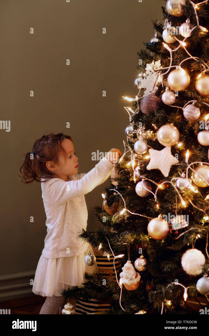 Girl decorating Christmas tree at home - Stock Image