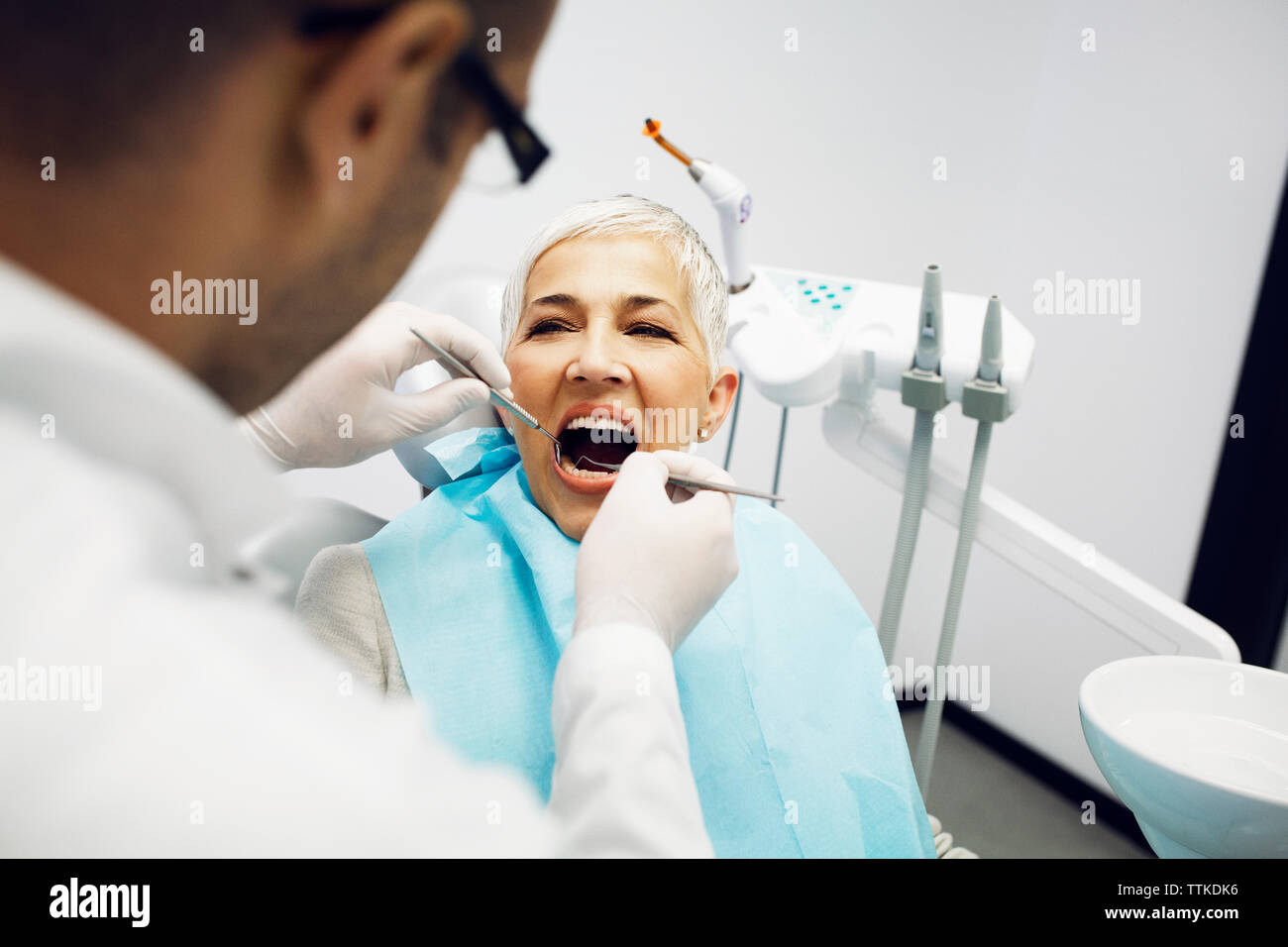 Male dentist examining patient's teeth at clinic Stock Photo