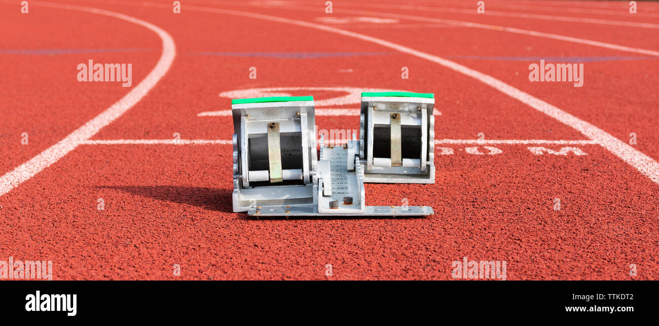 View from behind of a set of starting blocks in lane two on a red track. - Stock Image