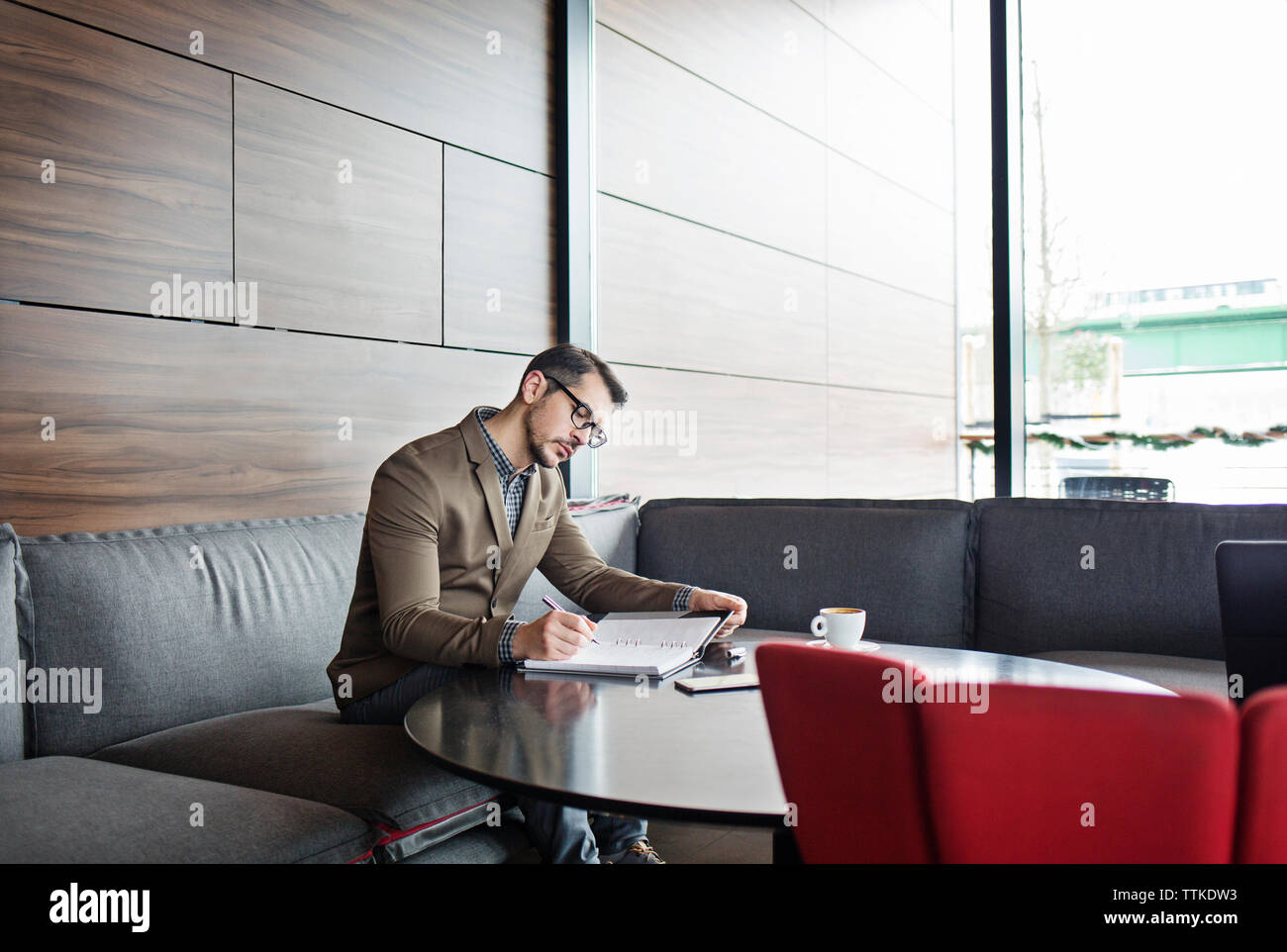 Businessman writing in diary at table in restaurant - Stock Image