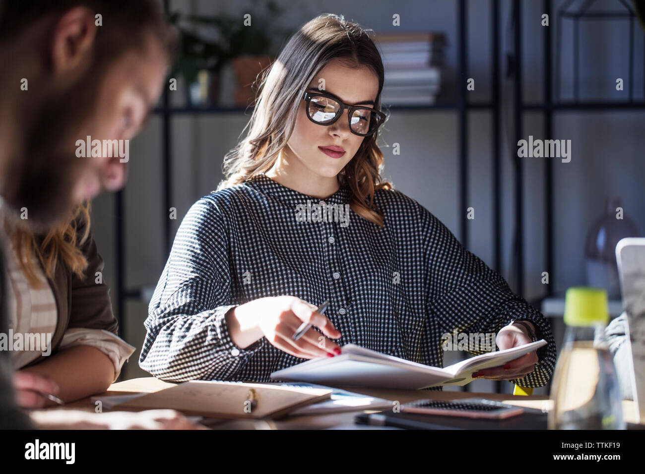 Woman studying while sitting with friends at table in classroom Stock Photo