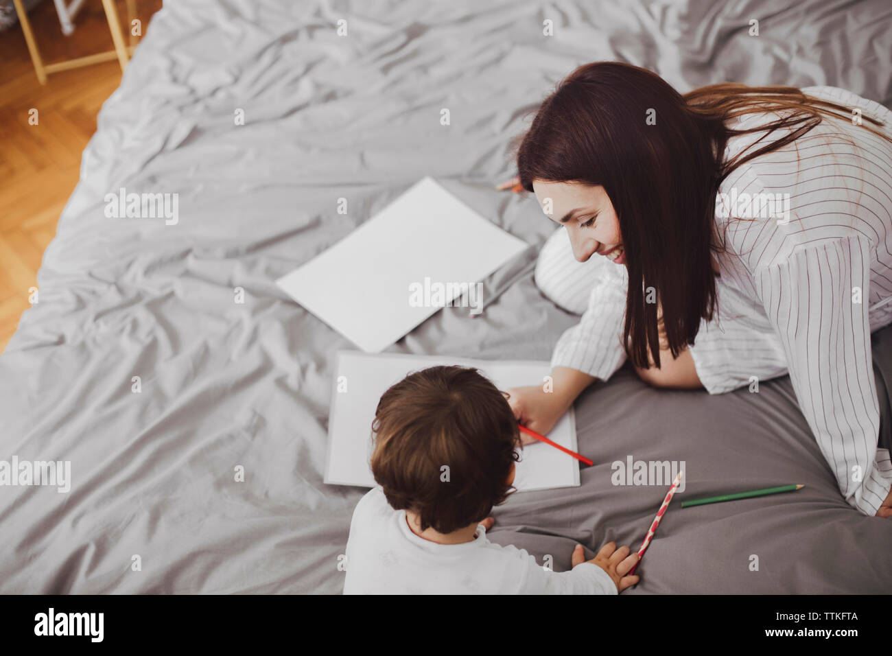High angle view of happy mother and baby boy with school supplies on bed at home Stock Photo