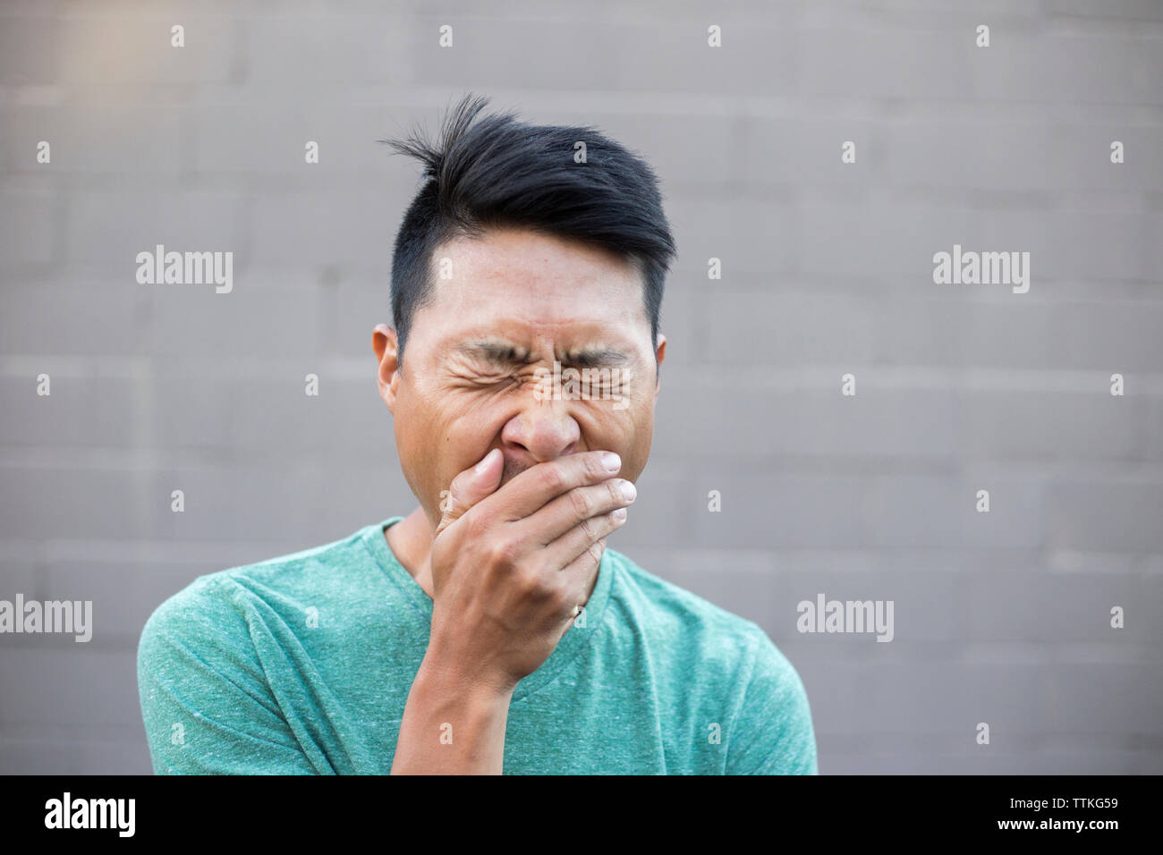 Close-up of man with hands covering mouth while yawning against wall - Stock Image