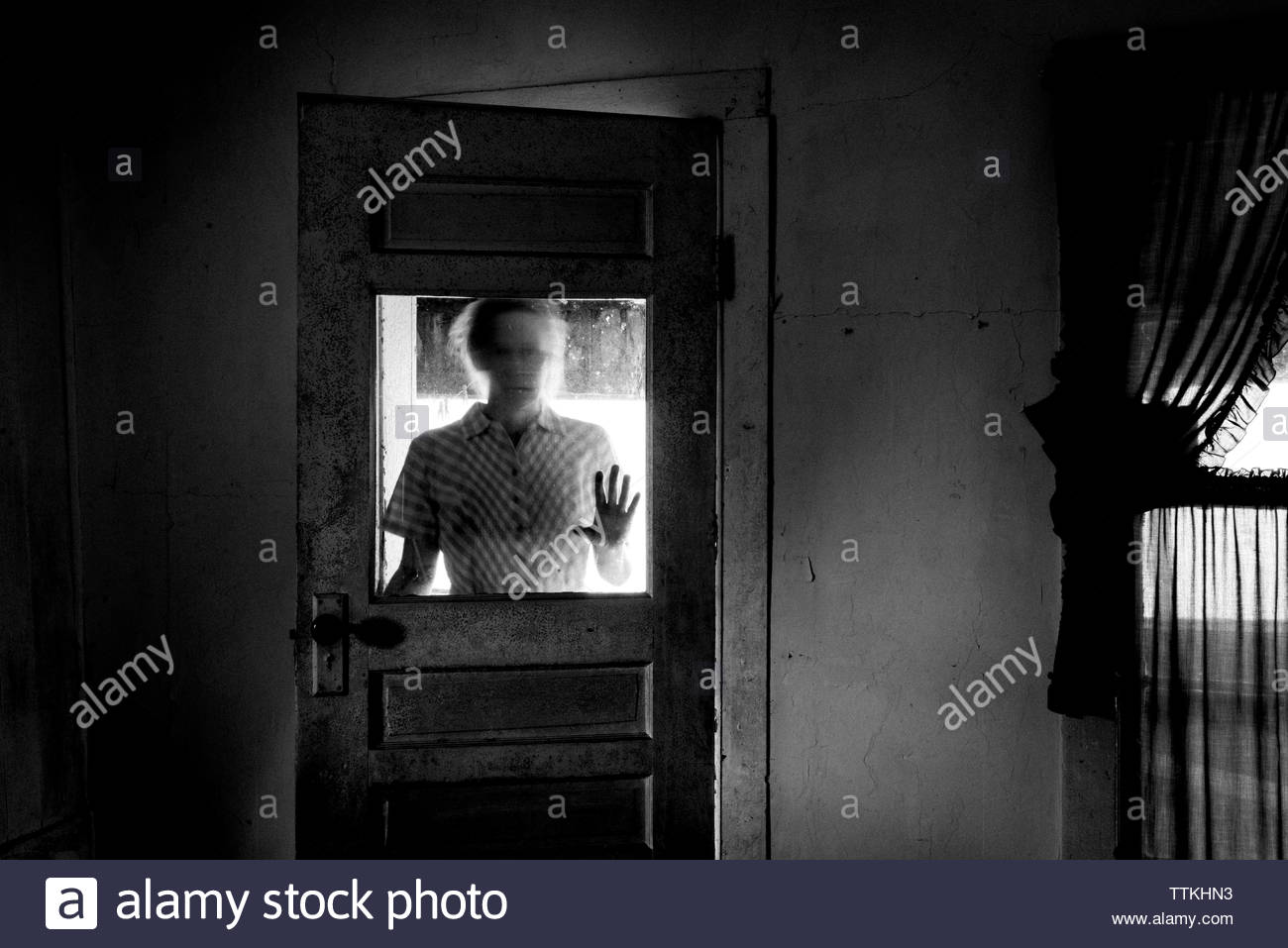 Woman standing by door at home - Stock Image