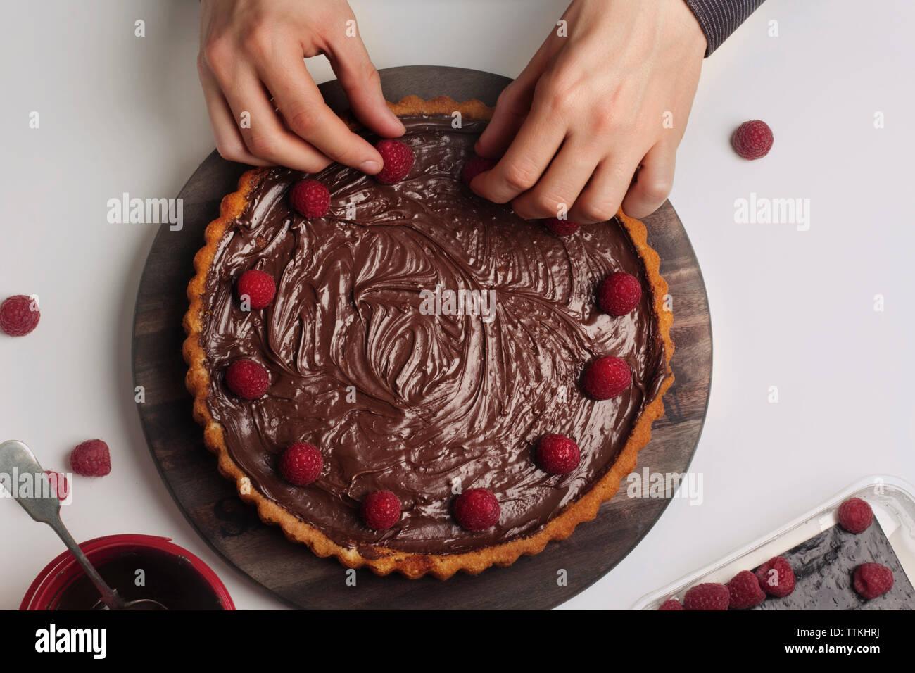 Man decorating chocolate tart with raspberries - Stock Image