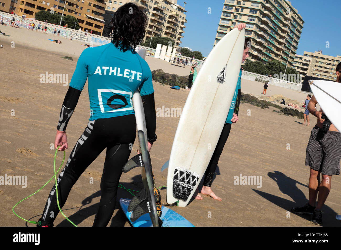 Boys surfers teens wearing wetsuits with surfboards stand and talk together on the beach at Matosinhos Porto in Portugal Europe EU  KATHY DEWITT Stock Photo