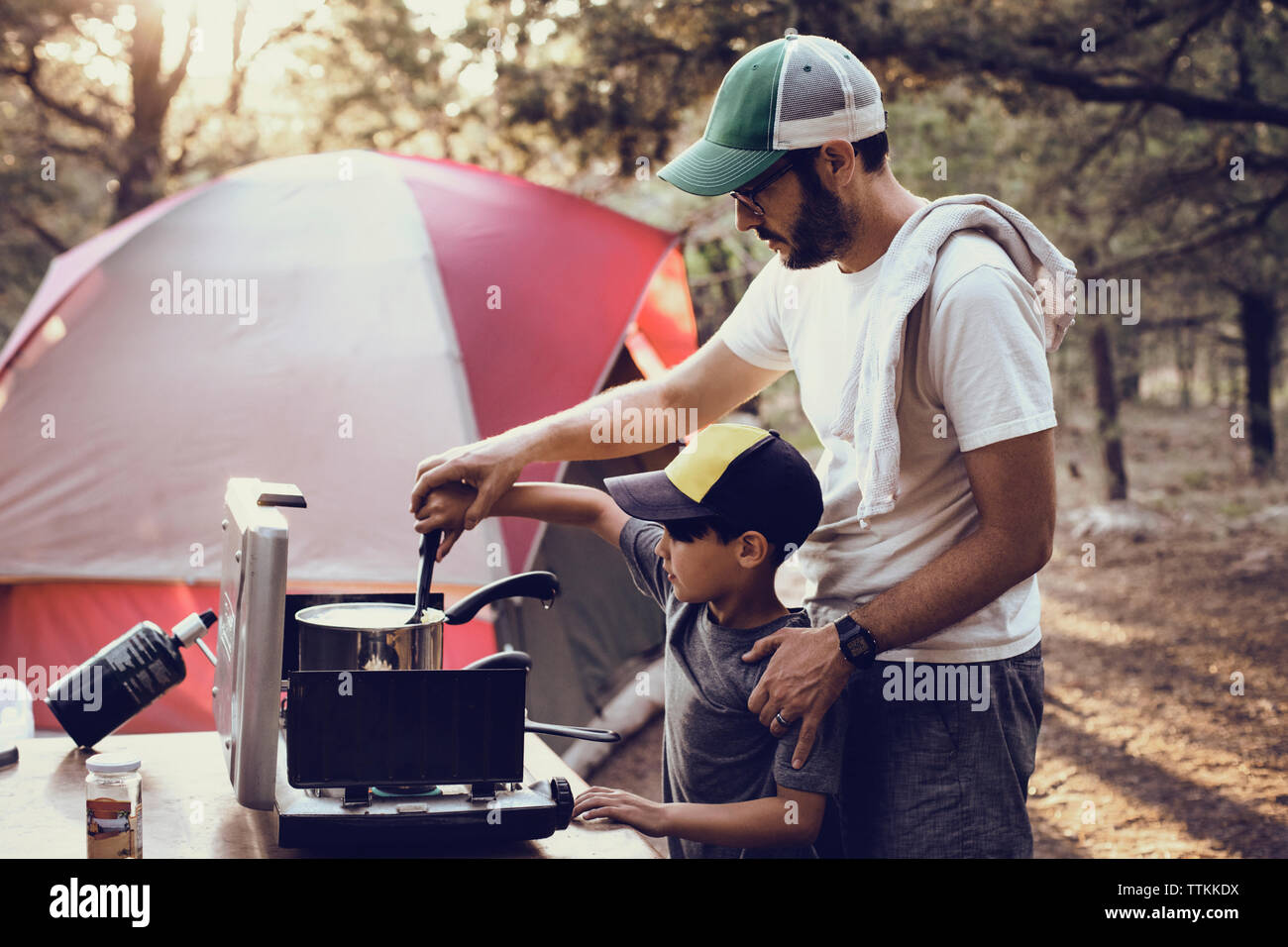 Father and son preparing food on camping stove in forest - Stock Image