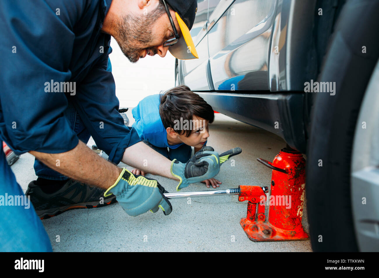 Father guiding son while using car jack to repair car at driveway - Stock Image